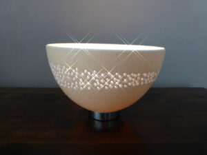 Image of a beautiful hand carved ostrich egg tealight. Carved from a half egg and mounted on a metal base. Features a pattern inspired by the Milky Way