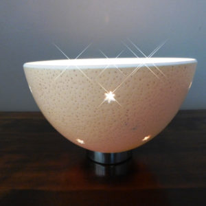 Image of a hand carved Ostrich Egg tealight, with a carved pattern of small stars